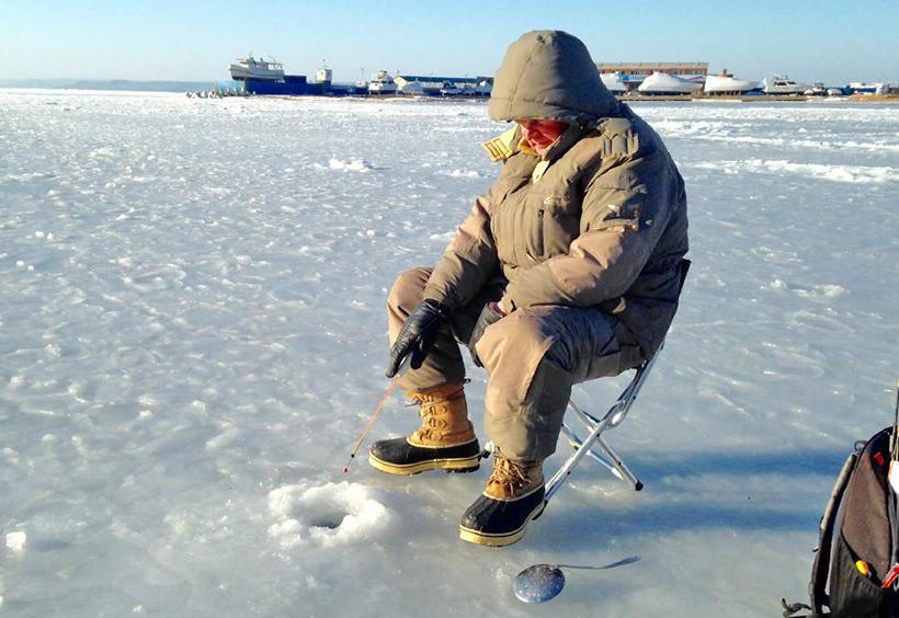 氷に穴をあけ釣り糸を垂らす釣り人
