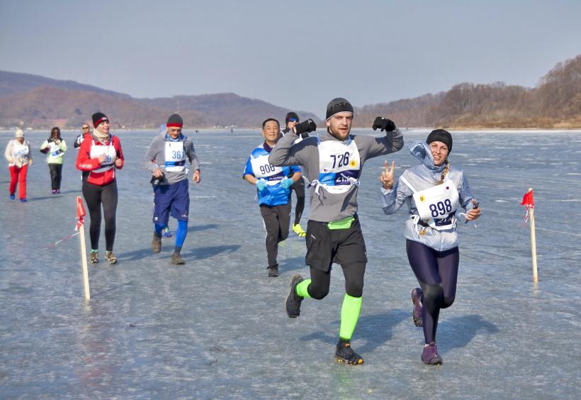 滑り止めスパイク付きのシューズと完全防寒具で氷原を走るランナー