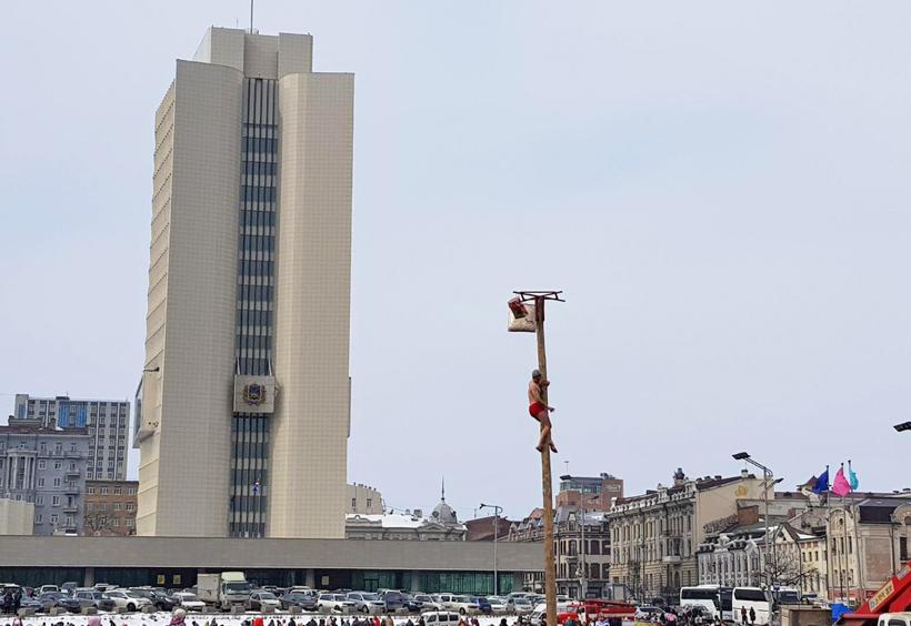 マースレニツァで棒を登る男性と見物客
