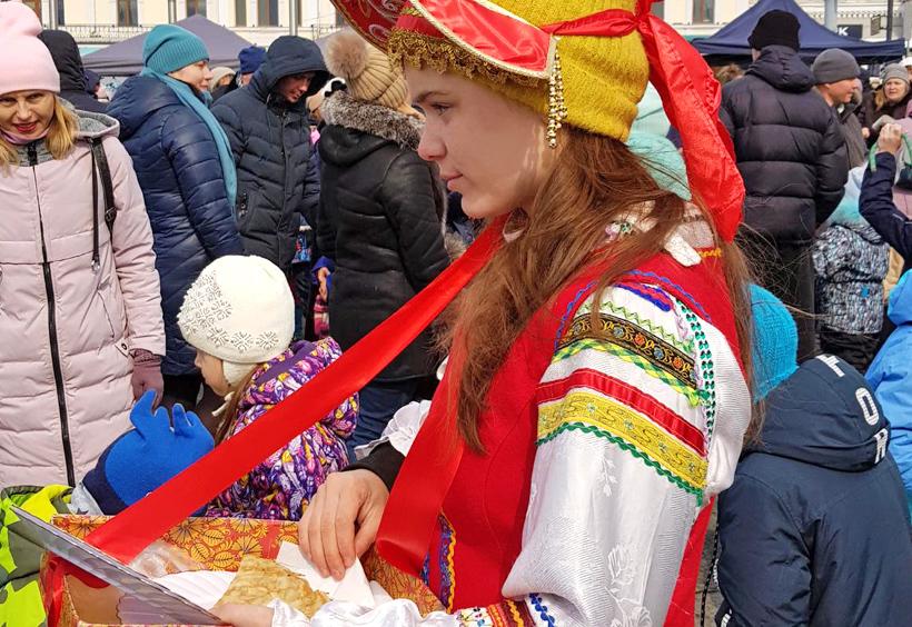 マースレニツァでブリヌィを配る民族衣装の女性
