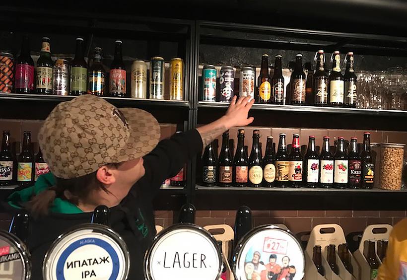 棚に並ぶビールを見せる店員男性