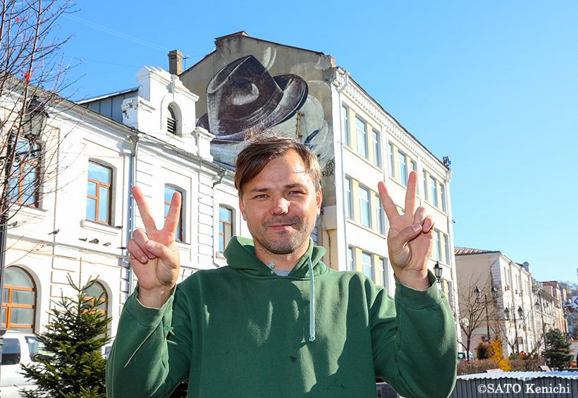 帽子の壁画前でポーズをとるパーヴェル・シュグロフさん