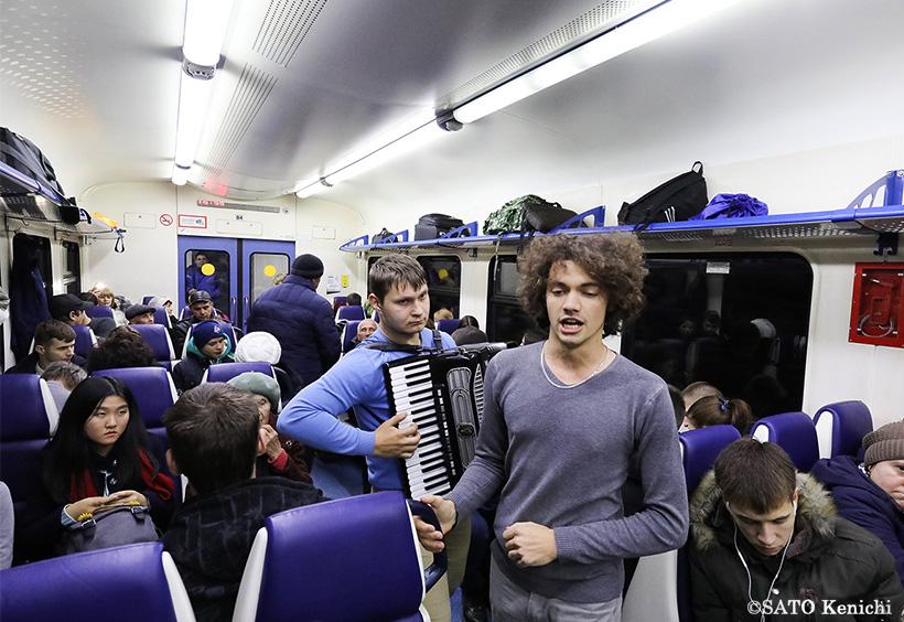 電車内で演奏する二人の青年