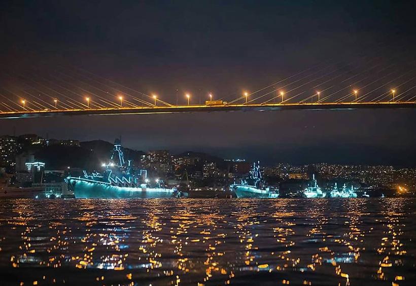 夜の海に浮かぶライトアップされた艦隊