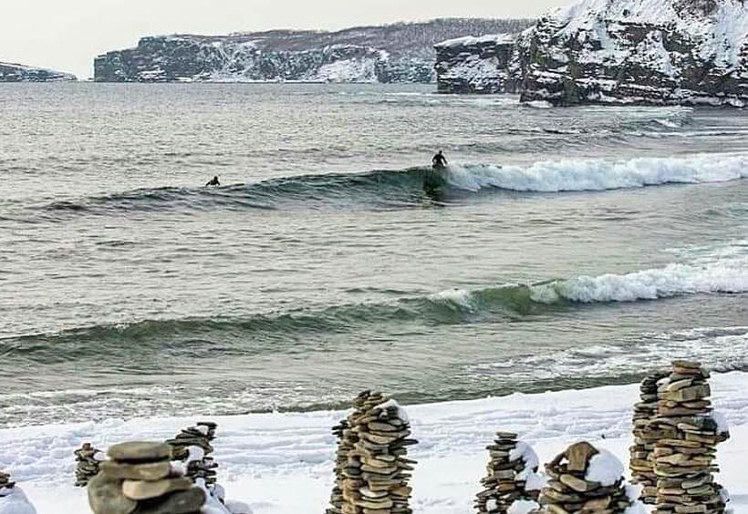 真冬の極寒のウラジオストクの海でサーフィンをするサーファー