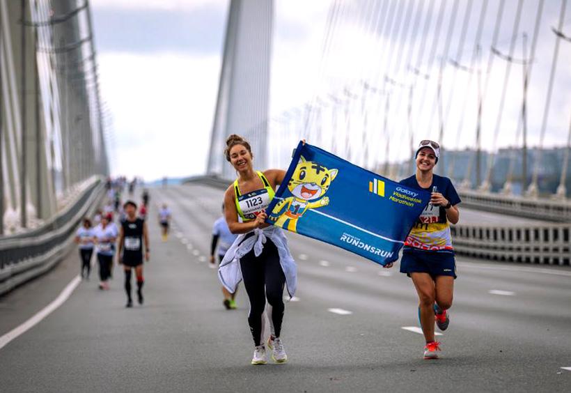 ウラジオストク国際マラソンでアムールタイガーの旗を持って走るランナー