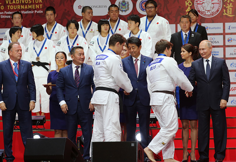 ウラジーミル・プーチン大統領と日本の安倍晋三総理大臣と握手する選手たち